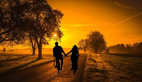 Couple cycling into the sunset